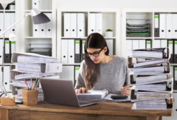 Young Businesswoman Wearing Eyeglasses Calculating Bill In Office